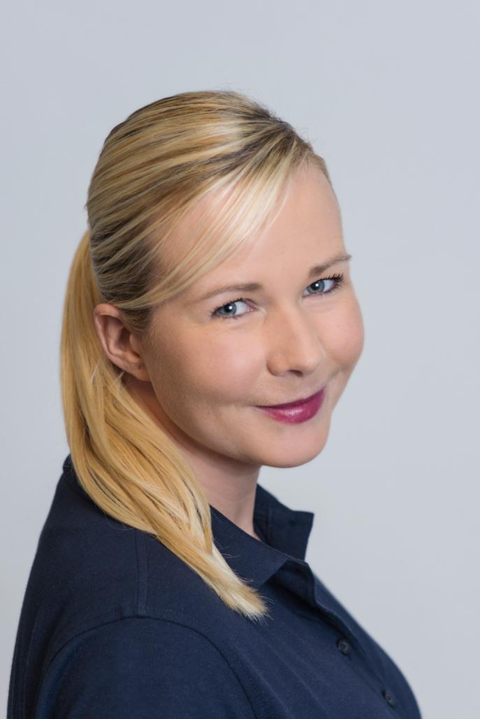 Ein Portraitbild von Julia Schenke. Sie trägt ein blaues Poloshirt!