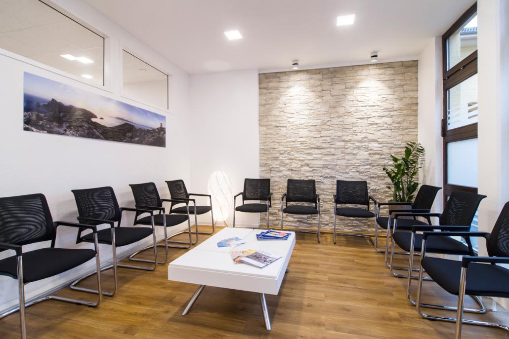 Bild vom hellem Wartebereich mit Stühlen Beistelltische und schönen Bildern an der Wand